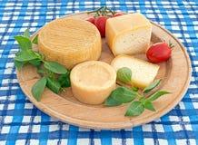 Rundes, Kreis-cheeseboard mit Käse auf blauer Tischdecke Stockfotos