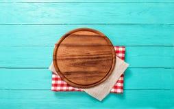 Rundes Schneidebrett auf rotem Plaid und grauer Tischdecke Blauer hölzerner Hintergrund im Restaurant Draufsicht- und Kopienraum Stockfotografie