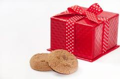Rundes Schokoladenplätzchen und rote Geschenkbox mit Bogen Lizenzfreie Stockbilder