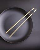 Rundes Schwarzblech mit Essstäbchen für Sushi Stockfotos
