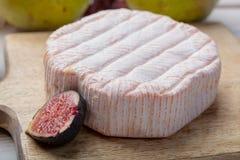 Rundes St?ck franz?sischer K?se Fleur Rouge gemacht von der Kuhmilch gedient als Nachtisch mit frischen Feigen und Birnen lizenzfreie stockbilder