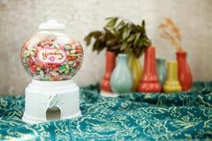 Rundes transparentes Blasenverkaufsüßigkeits-Maschinenspielzeug auf einem bunten Hintergrund Lizenzfreie Stockfotografie