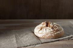 Rundes Weizenroggenbrot liegt auf Sackleinen auf einem hölzernen Hintergrund Lizenzfreies Stockfoto