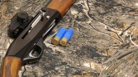 rundor 12-gauge och en camohagelgevär royaltyfri fotografi