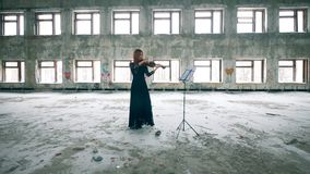 Rundown building with a woman playing the violin in it. 4K stock video footage