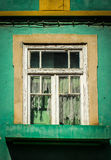 Rundown house with colourful facade. And torn curtains in a city in portugal Stock Image