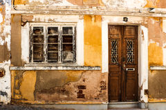 Rundown house with yellow facade. And wooden doors in a city in portugal Stock Photos