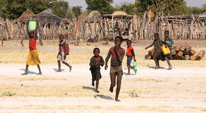 RUNDU NAMIBIA - SEPTEMBER 19: Oidentifierade barn som hämtar wa fotografering för bildbyråer