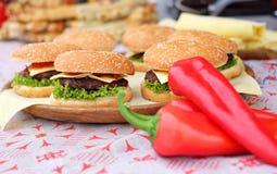 Rundvlees en kaasburgers met groene salade en saus die op een houten plaat bij het festival van het straatvoedsel liggen Royalty-vrije Stock Foto