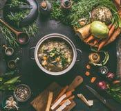 Rundvlees en koolsoep of hutspot in gietijzer kokende pot op donkere achtergrond met lage carburatorgroenten, kruideningrediënten royalty-vrije stock afbeeldingen