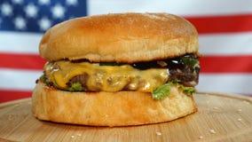 Rundvlees sappige hamburger met kaas, saus en groenten die op een houten raad voor Amerikaanse Vlag roteren stock videobeelden