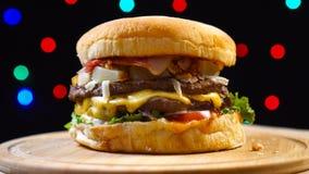 Rundvlees smakelijke hamburger die op kleurrijke vage lichtenachtergrond roteren stock videobeelden