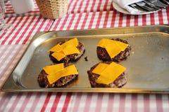 Rundvlees of varkensvleesburgers van de vleesbarbecue met cheddarkaas stock afbeelding