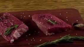 Rundvleesfilet op een bureau met peper, rozemarijn en knoflook stock video