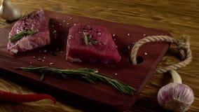 Rundvleesfilet op een bureau met peper, rozemarijn en knoflook stock footage
