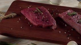 Rundvleesfilet op een bureau met peper, rozemarijnbijl en knoflook stock video