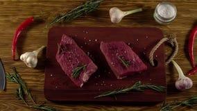 Rundvleesfilet op een bureau met peper, rozemarijnbijl en knoflook stock footage