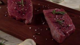 Rundvleesfilet op een bureau met peper, rozemarijnbijl en knoflook stock videobeelden