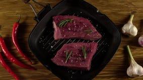 Rundvleesfilet op een pan met peper, rozemarijn en knoflook stock videobeelden