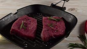 Rundvleesfilet op een pan met peper, rozemarijn, olie en knoflook stock videobeelden