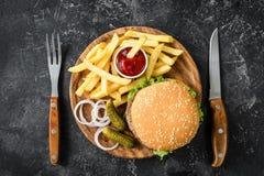 Rundvleeshamburger, frieten, groenten in het zuur, ui en ketchup stock fotografie