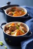Rundvleeshutspot met aardappel en wortel in blauwe potten Stock Foto