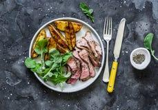 Rundvleeslapje vlees en gebakken jonge aardappels - heerlijke lunch op een donkere achtergrond, hoogste mening stock foto