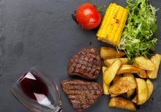 Rundvleeslapje vlees met geroosterde aardappel, graan, salade en rode wijn stock fotografie