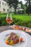 Rundvleeslapje vlees met saus en groenten, met batatengebraden gerechten en glas van wijn, productfotografie voor restaurant en g stock afbeeldingen