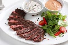 Rundvleeslapje vlees, middelgrote zeldzaam, met verse groenten, kruiden en saus Stock Foto's