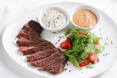 Rundvleeslapje vlees, middelgrote zeldzaam, met verse groenten, kruiden en saus Stock Fotografie
