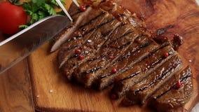 Rundvleeslapje vlees op de raad met een messen langzame motie die wordt gesneden stock videobeelden