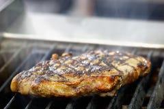 Rundvleeslapjes vlees op de grill met rook Stock Afbeeldingen