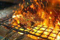 Rundvleeslapjes vlees op de grill met vlammen Geroosterd vlees in barbecue met vlammen en steenkolen Grillvlees stock foto's