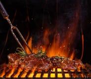 Rundvleeslapjes vlees op de grillrooster, vlammen op achtergrond Stock Foto