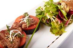 Rundvleesmedaillons op tomaat en geroosterde aubergine Stock Foto's