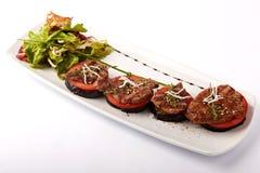 Rundvleesmedaillons op tomaat en geroosterde aubergine Stock Afbeelding