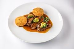 Rundvleeswangen in saus met broccoli en slabonen op een witte plaat Stock Afbeelding