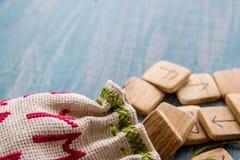 Rune antiche, borsa della tela con ricamo su vecchio fondo di legno d'annata Fuoco selettivo Fotografia Stock