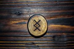 Rune Ingwaz Yngvi cinzelou da madeira em um fundo de madeira fotos de stock