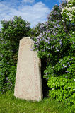Rune stone at lilacs Stock Photos