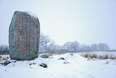 Rune-stone in winter landscape. A rune-stone from the viking age in a snowy landscape. The Karlevi stone Oland Sweden one of the most remarkable rune stones in Stock Image