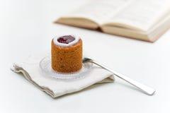 Runeberg-Torte auf Platte nahe bei Buch Stockfotografie