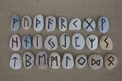 Runen- alfabet op gesneden stenen over het zand Stock Fotografie