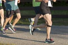 Runers, das ein 5000-Meter-Rennen im Sonnenschein läuft Stockbild