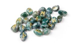 Runes. Golden Elder Futhark runes carved on blue-green stones, isolated on white Royalty Free Stock Photo