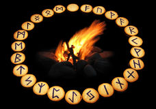 Runes around fire on black background Royalty Free Stock Image
