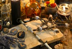 Runes, magic wand and pentagram on witch table Stock Photos