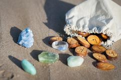 Runes on sand. Wood handmade runes and minerals on the sand Stock Image