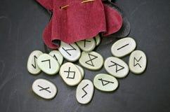 runes sur le conseil en bois noir photographie stock